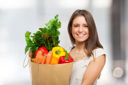 comprando: Mujer que sostiene una bolsa llena de alimentos frescos