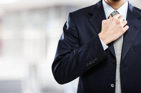Close-up of a businessman adjusting his necktie