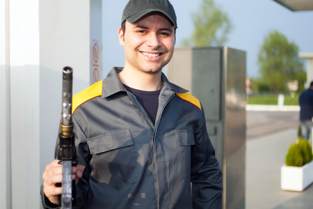 gas distribution: Smiling gas station attendant at work