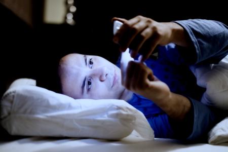 Man met behulp van zijn mobiele telefoon in het bed Stockfoto