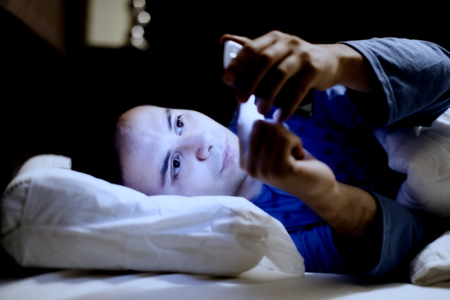 to phone: Man using his mobile phone in the bed Stock Photo