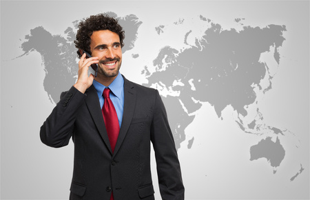 Smiling man talking on the phone in front of a world map photo