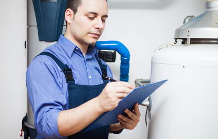 Technicus onderhoud van een boiler Stockfoto