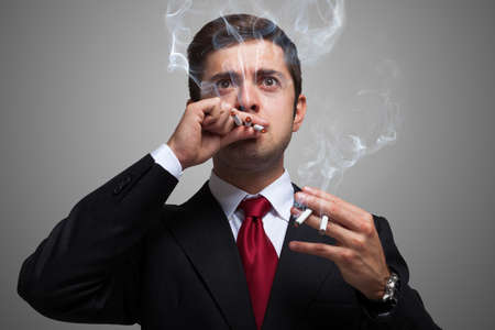 investor: Portrait of a nervous businessman smoking many cigarettes at once
