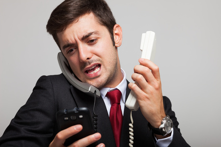 executive office: Stressed businessman talking on many phones at once Stock Photo