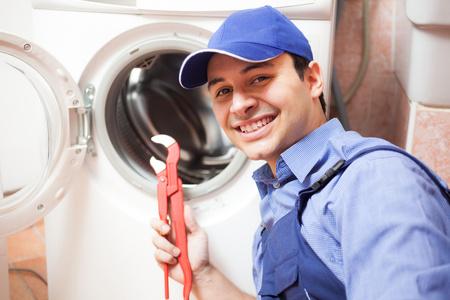 Smiling technician repairing a washing machine photo