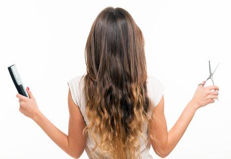 cabello rubio: Mujer con el pelo largo que sostiene un peine y tijeras