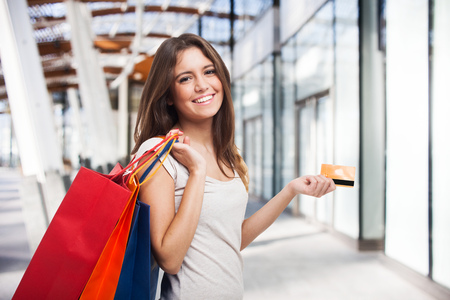 shopping center: Young beautiful woman holding shopping bags and a credit card
