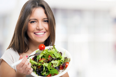 Young woman eating a healthy salad photo