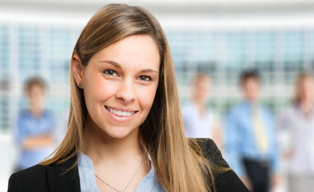 Successful business woman standing with her staff in background at office photo