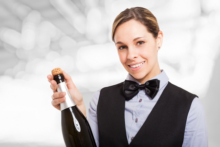 Portrait of a smiling female waiter holding a champagne bottle. Isolated on white photo