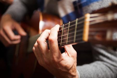 guitarra acustica: Detalle de un guitarrista tocando una guitarra clásica