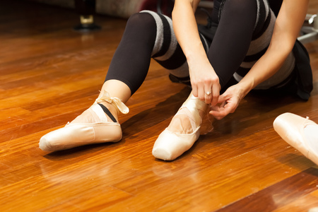 Ballerina puts on pointes while sitting on a wooden floor