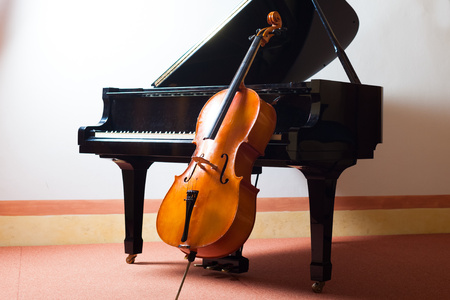 Classical music concept: violin leaning on a piano photo