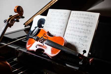 Classical music scene: violin and score on a piano