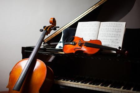 violines: Clásico concepto de la música: chelo, violín, piano y una partitura