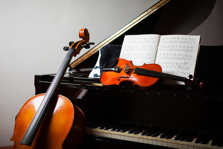 violins: Classical music concept: cello, violin, piano and a score