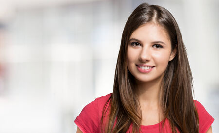 woman hairstyle: Portrait of a smiling woman against a bright background