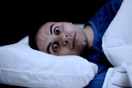 difficulties: Portrait of an insomniac man trying to sleep in his bed Stock Photo