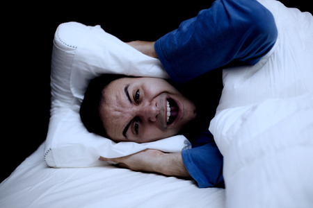transient: Insomniac man using a pillow to cover his ears