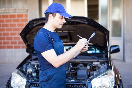 car maintenance: Smiling mechanic writing on a clipboard Stock Photo