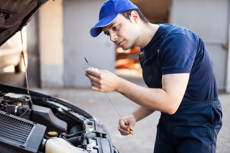 mineral oil: Mechanic checking the oil level in a car engine