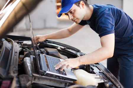 Skilled mechanic using a laptop computer to check a car engine Imagens