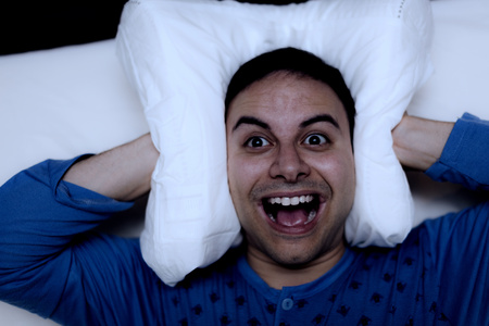 insomniac: Insomniac man using a pillow to cover his ears