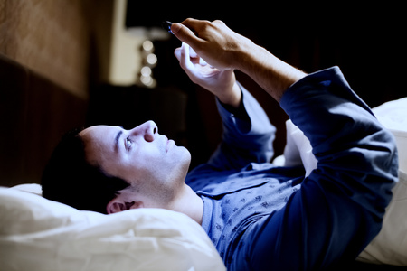 bed: Man using his mobile phone in the bed Stock Photo