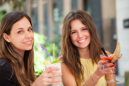 Portrait of two friends drinking a cocktail photo