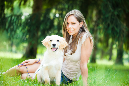 animal park: Young woman playing with her golden retriever puppy outdoors