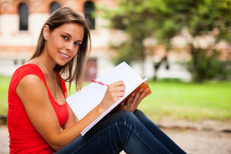 writing book: Woman studying while sitting outdoors Stock Photo