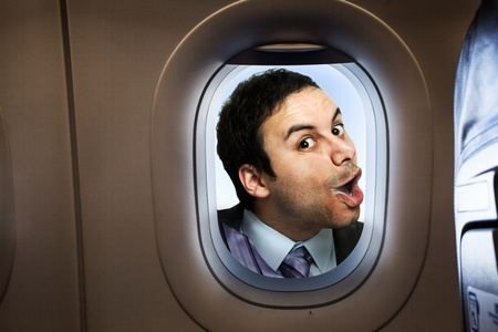 Businessman looking  through an airplane window Stock Photo
