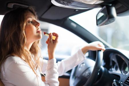 peligro: Mujer que usa el espejo retrovisor para aplicar el maquillaje mientras conduce su coche