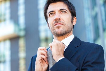 law suit: Confident businessman adjusting his necktie Stock Photo