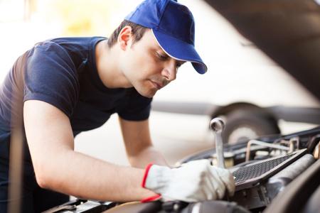 mecanico: Mec�nico con una llave de reparar un motor de coche Foto de archivo