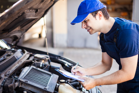 budget repair: Smiling mechanic writing on a clipboard Stock Photo