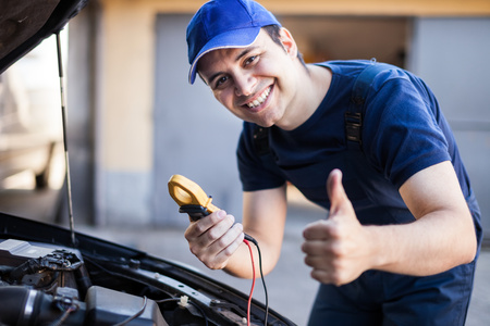 electrician tools: Smiling mechanic troubleshooting a car engine