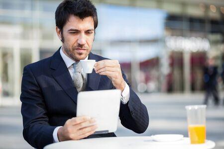 ejecutivos: El hombre de negocios la lectura de su tableta digital durante el desayuno Foto de archivo