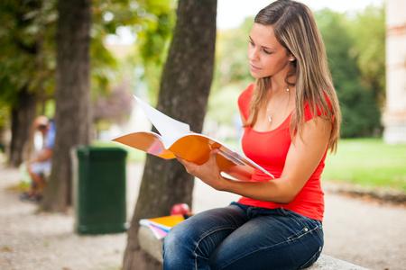 Frau studiert, während im Freien zu sitzen