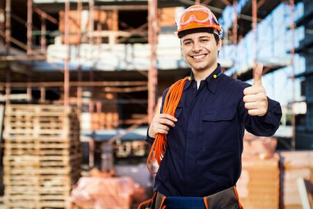 electrician tools: Portrait of a smiling worker in a construction site