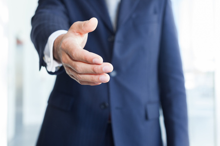 company employee: Close-up of a businessman offering an handshake
