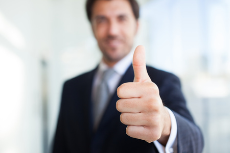 satisfied customer: Portrait of a smiling businessman giving thumbs up Stock Photo