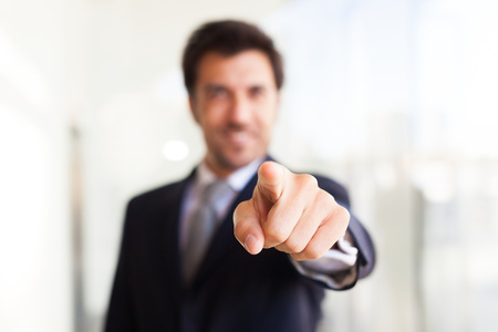 Lachend zakenman wijst zijn vinger op je Stockfoto