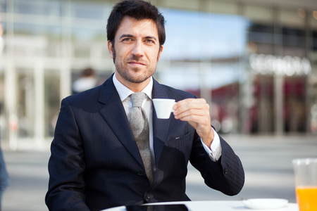 office environment: Portrait of a businessman drinking a coffee