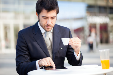 Businessman reading his digital tablet during breakfast photo