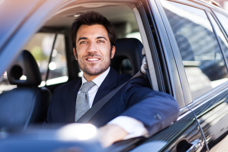 mature men: Portrait of an handsome smiling business man driving his car