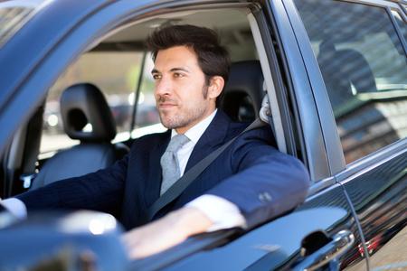 Retrato de um homem de negócio de sorriso bonito dirigindo seu carro