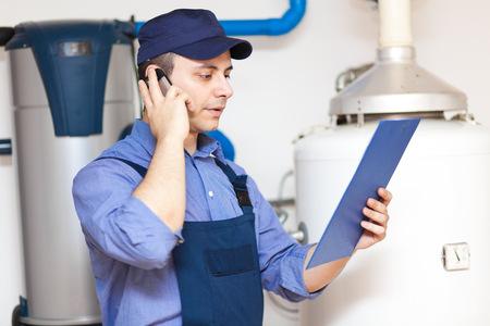 maintenance fitter: Plumber making a phone call