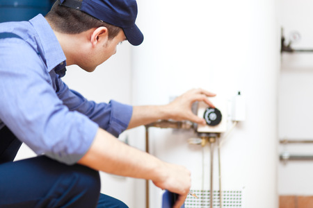 heater: Worker rotating a control knob Stock Photo